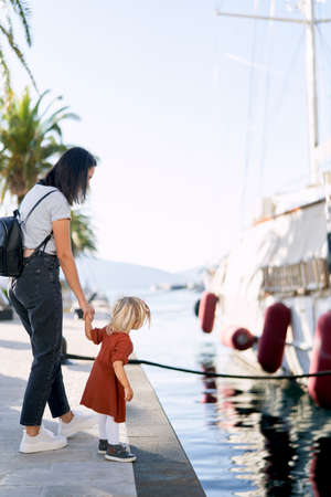 Mother and daughter are looking at a boat in a marina on a suuny day