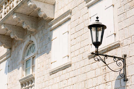 Close-up of a street lamp on the wall of a house under a balcony on a sunny day. Фото со стока
