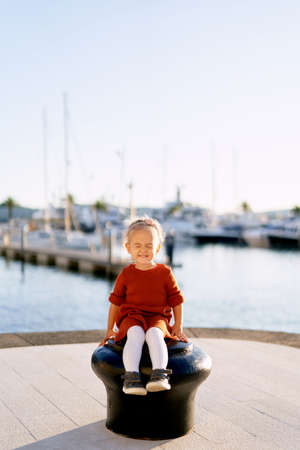A sweet little girl is smiling with her eyes closed while sitting on a pier by the sea Фото со стока