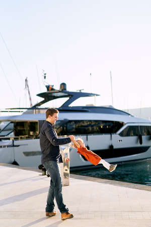 Father is whirling his baby girl in front of a big boat on a pier Фото со стока