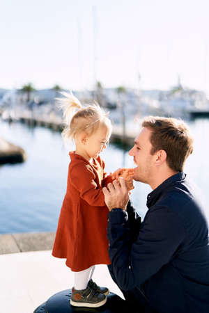 A cute toddler is playing with her dad on a boat pier on a sunny day