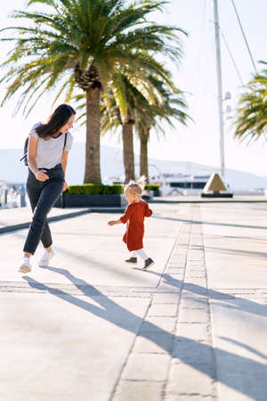 A cute 2-year old is running after her mommy among palm trees on a boat pier