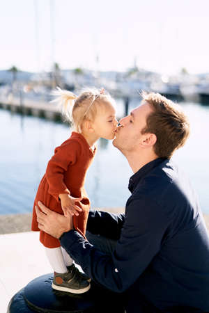Baby girl is kissing her daddy on a sunny day by the sea Фото со стока