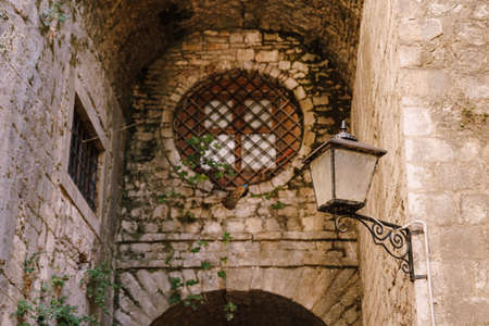 Antique hanging lantern in the wall of an old building with a window behind a round metal grate. Фото со стока