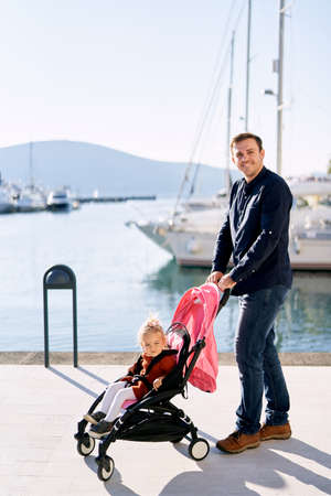 Father is pushing his daughter in a pink stroller on a boat pier in Montenegro Фото со стока