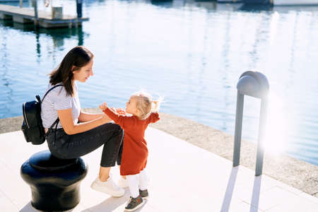 Woman is looking at her baby girl while sitting on a boat pier