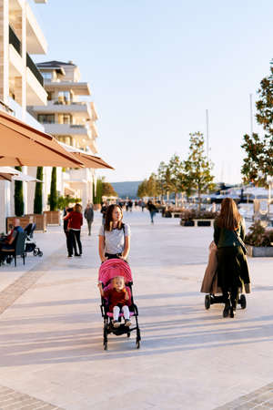 Mother is pushing her child in a pink stroller while walking on a boat pier in Porto Montenegro Фото со стока