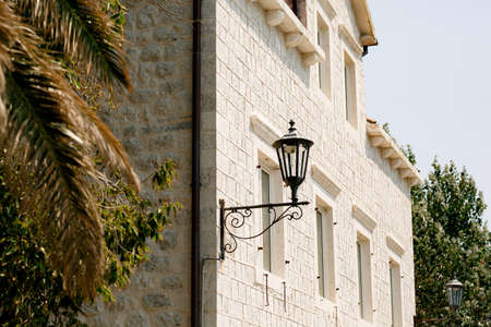 White brick building with street lamps at night in Perast. Фото со стока