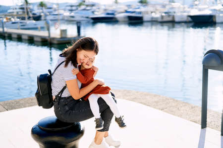 Young woman is hugging her daughter tight while sitting on a pier in a marina