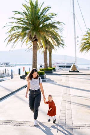 Mom and daughter are running and having fun on a boat pier by the sea