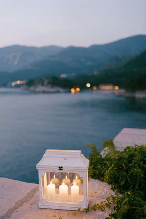 A candlestick-lantern with three lighted candles by ivy branches on a stone border against the background of mountains and water.