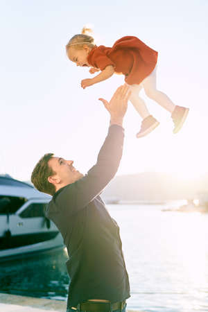 Father is throwing his 2-year old daughter in the air at sunset