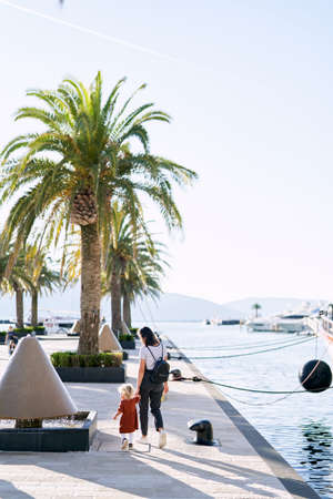 Young mother is walking hand in hand with her baby girl by the palm trees on a boat pier Фото со стока
