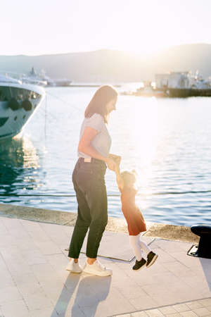Mother is whirling her daughter on a boat pier at sunset