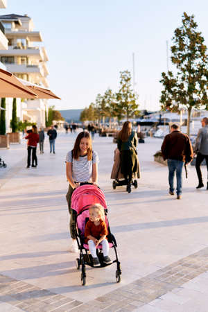 Woman is pushing a pink stroller with her daughter sitting inside of it while having a walk on a boat pier in Montenegro