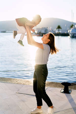 Mother is throwing her daughter in the air by the sea at sunset