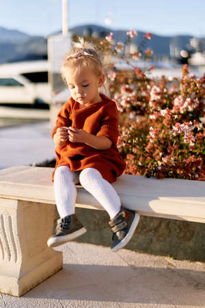 A 2-year old girl is sitting on a bench on a boat pier by the sea Фото со стока