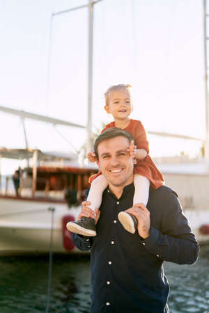Father is carrying his baby girl on his shoulders in front of a big boat in a marina