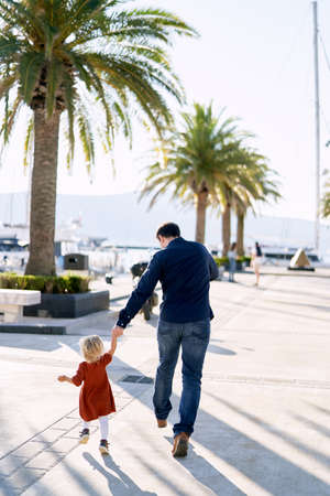 Man is running hand in hand with his toddler on a boat pier in Montenegro