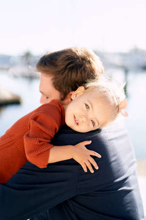 A portrait of a sweet girl hugging her father by the sea