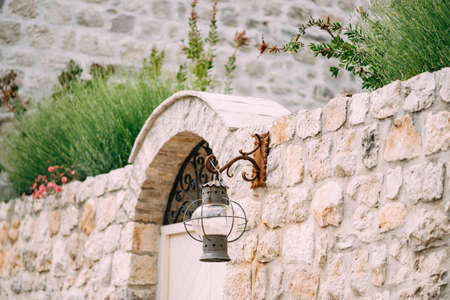 An antique hanging lantern on a rusty hook on a stone fence in Perast, Montenegro. Фото со стока