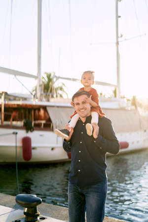 Little girl is sitting on her daddys shoulders on a boat pier in Porto Montenegro