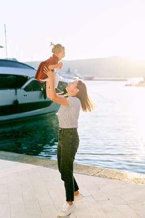 Mother is throwing her 2-year old in the air on a boat pier in Montenegro
