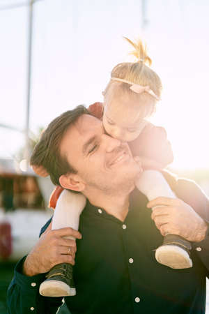2-year old is sitting on her fathers shoulders and kissing him on the cheek Фото со стока