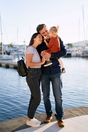 Beautiful family is hugging each other and enjoying a sunny day on a boat pier by the sea Фото со стока