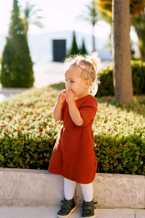 Pretty little girl in a terracotta colored dress and white tights is snacking on a pie in a park on a sunny day