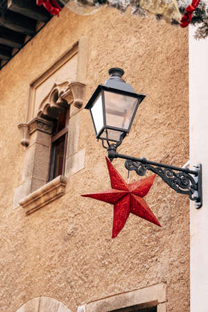 A street lamp on a bracket on the wall of a house with a red star at the window with patterns in stone. Фото со стока