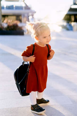 Little girl in a terracotta dress is carrying a big black backpack on her back Фото со стока