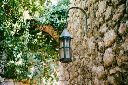 Street lamp near trees on a stone wall in Old Bar town in Montenegro.