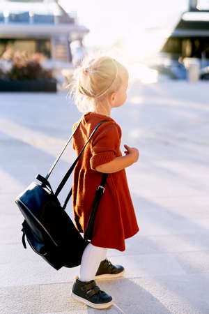 A cute 2-year old is carrying a big black backpack on her back while walking on a boat pier