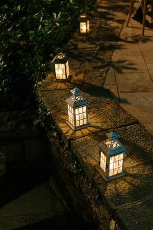Candlesticks lanterns at night on a stone fence.