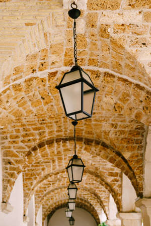 Close-up of lanterns on an arched brick ceiling. Фото со стока