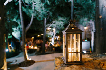 Close-up of a lantern candlestick with a candle inside on a stone texture in a courtyard with trees and people.