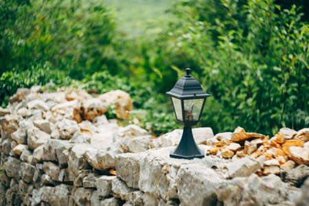 Street lamp on a stone fence against a background of green plants.