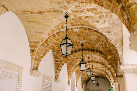 Hanging lights in the arched opening of the corridor on the ceiling. Фото со стока