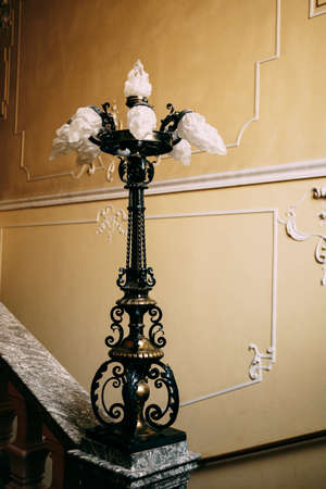 Antique antique lamp on the stair railings against the patterned wall. Фото со стока