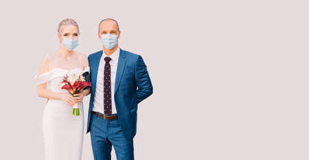 Bride and groom in medical masks on an isolated background. Wedding for two during isolation, Covid-19 pandemic. Banner with copyspace and bride and grooms portraits