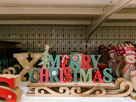 Budva, Montenegro - 15 December 2020: Wooden toy decoration in the shape of a sleigh with a multicolored inscription MERRY CHRISTMAS