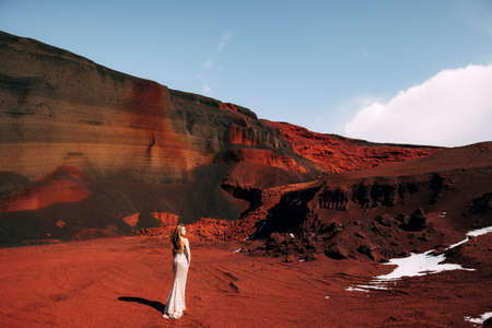 The girl is standing with her back. Portrait of a bride model in a golden wedding evening dress, in a yellow-red sandy quarry, in the crater of a volcano in Iceland, Golden Circle. Imagens