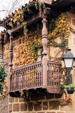 A wooden balcony with columns entwined with yellow-green vines in the Spanish village - Poble Espanyol