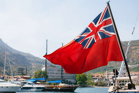 Close-up of the British Red Ensign aboard a ship with ships and mountains in the background. Red flag with the first version of Union Jack in the upper left corner.