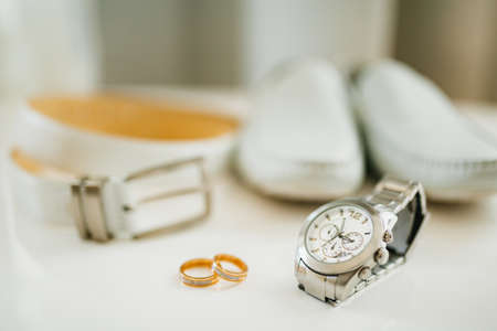 Close-up of wedding rings of the bride and groom on a white background with a wrist watch, white belt and mens loafers.