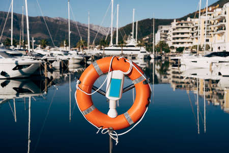 A close-up of a lifebuoy on a stand on the dock overlooking the mountains and yachts on the water. Marina for yachts in Montenegro, in Tivat, near Porto Montenegro. Imagens