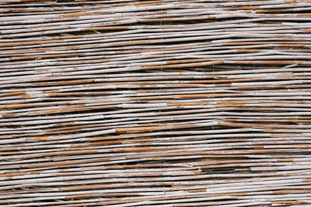 Close-up texture of a fence made of bamboo twigs.