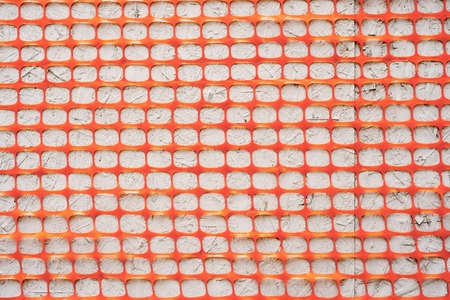Texture Orange fence construction mesh close-up on a gray background. Imagens