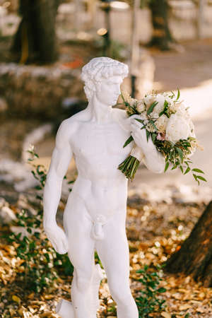 Greek antique sculpture of a young stately David with the brides wedding bouquet. Imagens